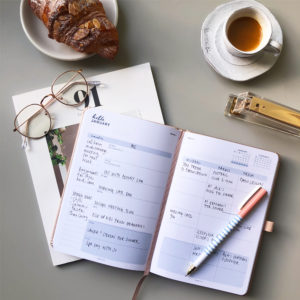 diary on a table with a pen and a coffee