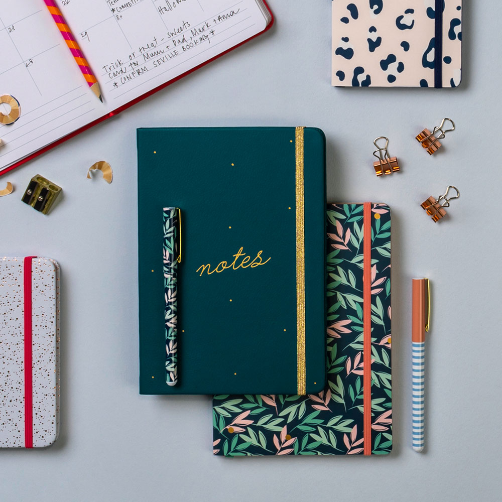 Notebook and pen to show a place where you could monitor your social media usage.
