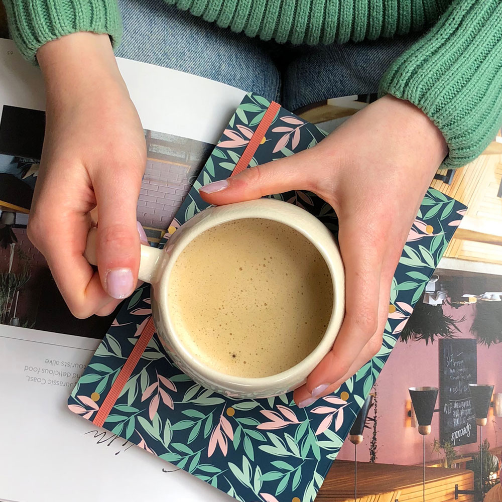 A hand holding a cup of coffee on top of a notebook.