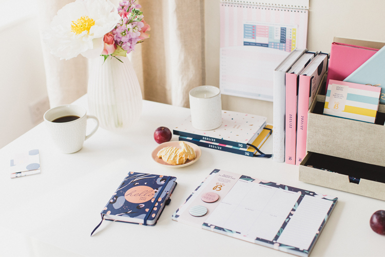A student desk setup featuring Busy B products such as the Mid Year Calendar, Mid Year A6 To Do Diary and Weekly Planner Pad.