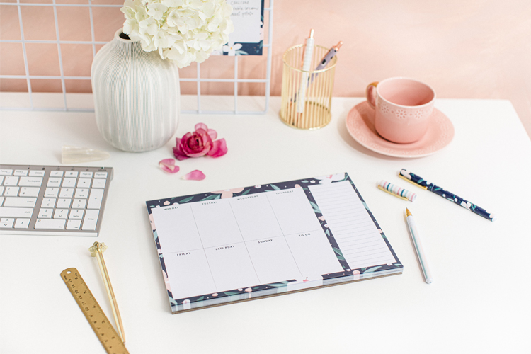 A navy Weekly Planner Pad sitting on a white desk. There are pens, a keyboard, a pink cup and saucer and a white vase of white flowers also sitting on the desk.
